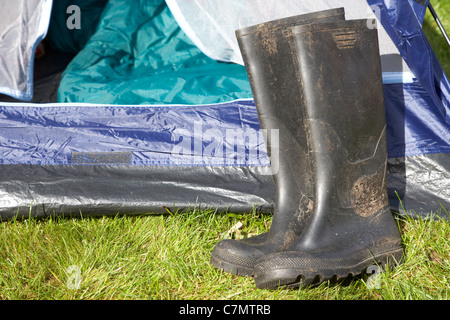 dirty wellington boots lying in front of an open tent door - Stock Photo