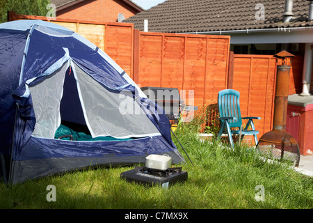 front door left open on a small dome tent pitched in the garden of the house in the uk - Stock Photo