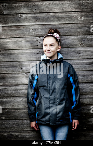 A young girl smiling and leaning against a wooden fence. - Stock Photo