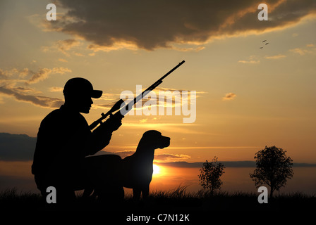 Hunter with his dog silhouettes on sunset background - Stock Photo