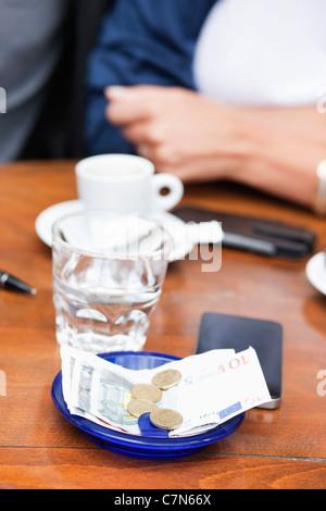 Euro banknotes and coins with bill on a table in a restaurant, Paris, Ile-de-France, France - Stock Photo