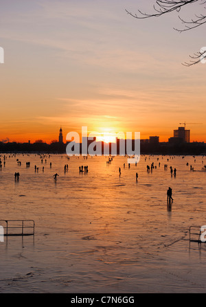 Firmly frozen Aussenalster, Outer Alster Lake, after sunset, people, amusement, ice, snow, winter, Hamburg, Germany - Stock Photo