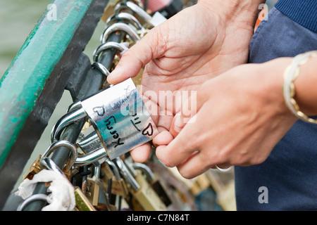 Couple locking a padlock of love on a bridge, Pont des Arts, Paris, Ile-de-France, France - Stock Photo