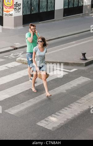 Couple walking on a road, Paris, Ile-de-France, France - Stock Photo