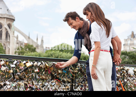 Couple locking a padlock of love on a bridge, Pont des Arts, Notre Dame de Paris, Paris, Ile-de-France, France - Stock Photo