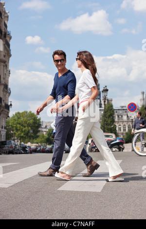 Couple crossing the road, Paris, Ile-de-France, France - Stock Photo