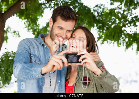 Couple taking a picture of themselves with a digital camera, Paris, Ile-de-France, France - Stock Photo