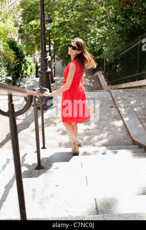 Woman moving down staircases and smiling, Montmartre, Paris, Ile-de-France, France - Stock Photo