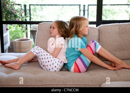 two girls sitting on the couch back to back - Stock Photo