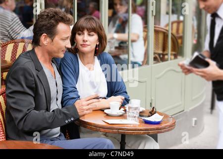 Couple sitting in a restaurant, Paris, Ile-de-France, France - Stock Photo