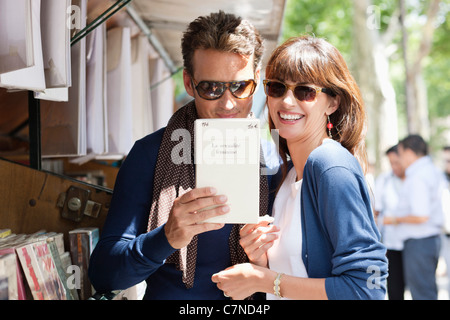 Couple at a book stall, Paris, Ile-de-France, France - Stock Photo