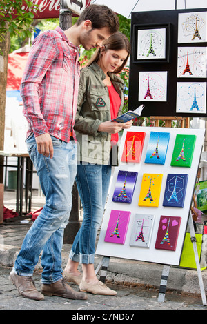Couple looking at postcards of Eiffel Tower at a market stall, Paris, Ile-de-France, France - Stock Photo