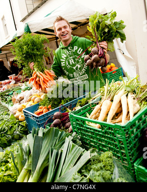 A young man selling Organic locally grown vegetables on sale at Aberystwyth Food Fair, September 2011, Wales UK - Stock Photo