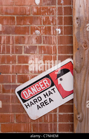 A warning sign that reads DANGER HARD HAT AREA. - Stock Photo
