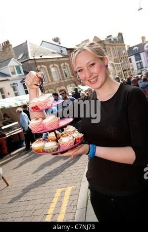 A young woman selling fresh made cup cakes at Aberystwyth Food Fair, September 2011, Wales UK - Stock Photo