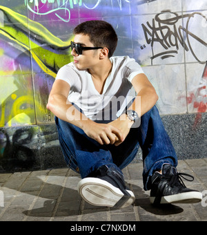 young man sitting in front of a colorful graffiti wall - Stock Photo