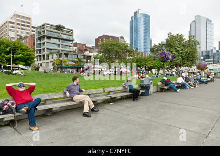 people enjoy sitting & lying on row of benches or raised lawn area of Victor Steinbrueck Park against backdrop of - Stock Photo