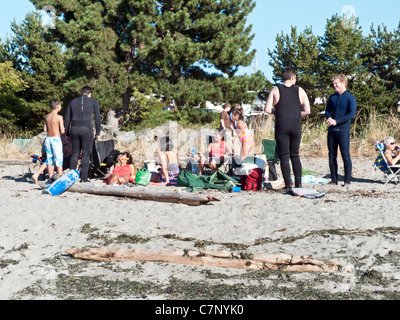 relaxed group of scuba divers with multi ethnic wives & children gathered at staging area on sandy beach Edmonds - Stock Photo
