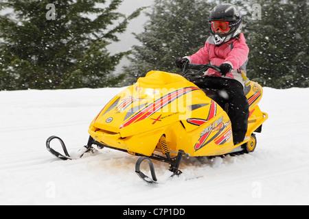 child riding a mini Snowmobile - Stock Photo