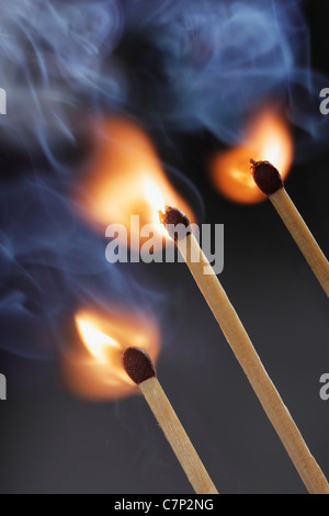 Three safety matches igniting simultaneosly - Stock Photo