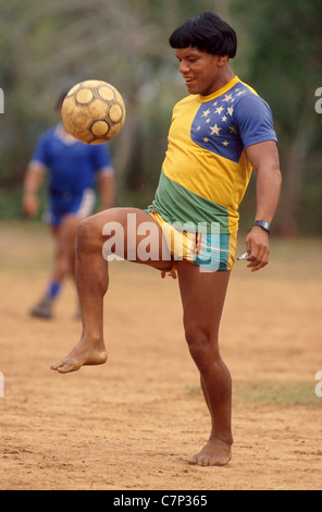 Acculturated Brazilian indian Yaulapiti indigenous people play soccer and wears Brazil soccer team shirt and watch - Stock Photo