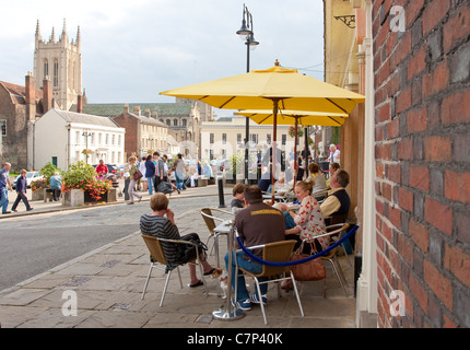 People sitting in an outside cafe in Angel Hill, Bury St Edmunds - Stock Photo