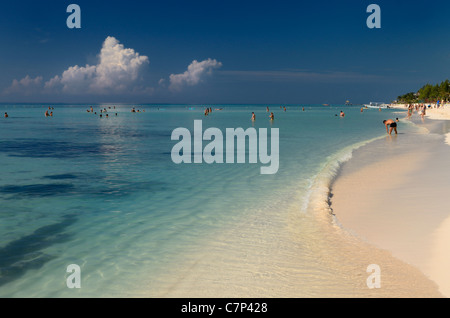 Swimmers in calm blue waters on the white sand beach of a Mayan Riviera resort Mexico - Stock Photo
