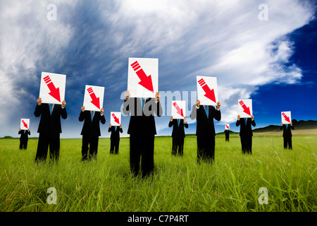 group of businessman in black suit and holding red arrow down graph - Stock Photo
