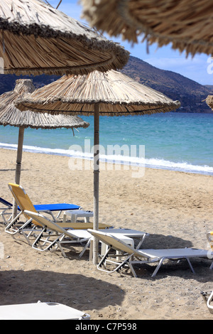 Empty chairs and umbrellas on the beach - Stock Photo