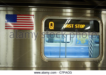People standing on a platform in a subway station with a blurred train passing by in Manhattan New York - Stock Photo