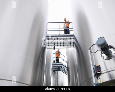 Workers checking tanks in bottling plant - Stock Photo