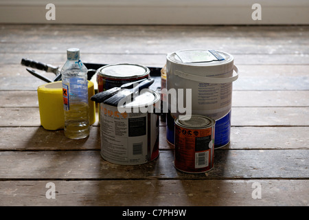 Paint cans and brushes in empty house - Stock Photo