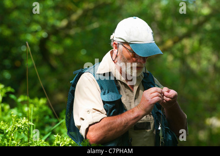 Fisherman tying on fly - Stock Photo