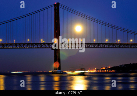 Portugal, Lisbon: Nocturnal illuminated Ponte 25 de Abril with full moon - Stock Photo