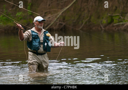 Fly fisherman casting a line in river - Stock Photo