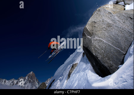 Skier jumping over steep mountain face - Stock Photo