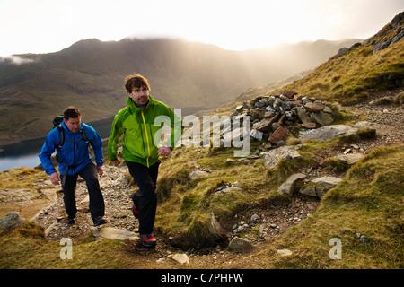 Men hiking on rocky mountainside - Stock Photo