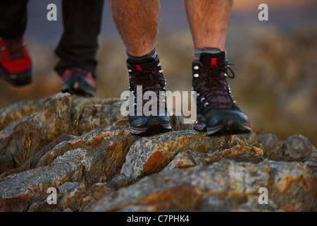 Close up of hiking boots on mountainside - Stock Photo