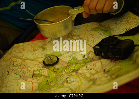 Man eating and examining trail map - Stock Photo