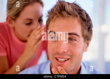Woman whispering in man's ear - Stock Photo