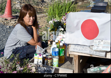 Miho Suzuki, 43, whose daughter Kana and 73 school mates were swept away by the March tsunami, kneels at a shrine - Stock Photo