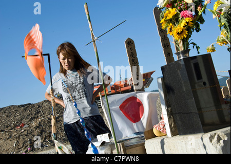 Miho Suzuki, 43, whose daughter Kana was swept away during the tsunami prays at a shrine by the school her daughter - Stock Photo