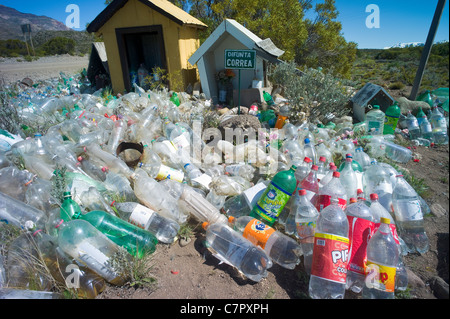 Difunta Correa roadside alter with empty bottles filled with water as offing, Patagonia, Chile - Stock Photo