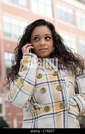 An attractive Indian woman talking on her cell phone in the city. - Stock Photo
