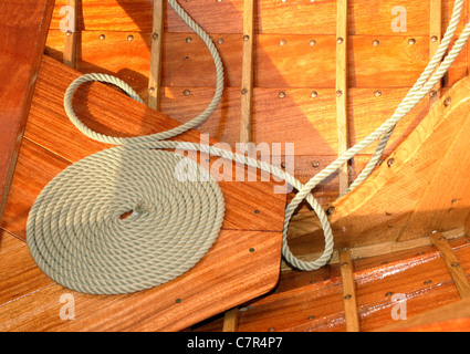 Coiled rope on teak deck. Decorative coiling is called 'cheesing' or 'flemish coil' and was used to help rope dry. - Stock Photo