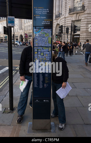 Two visitors to London read a street direction map in the capital's Regent Street. - Stock Photo