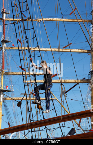 Young sailor entering the rig on Lilla Dan for work in the heights in the port of Copenhagen. Rig of Dar Mlodziezy - Stock Photo