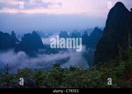 Karst hills in morning mist, Li River area, Yangshuo, Guangxi Province, China - Stock Photo