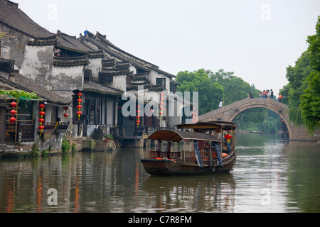 Rowing boat on the Grand Canal, old residence on the river bank, Xitang, Zhejiang Province, China - Stock Photo