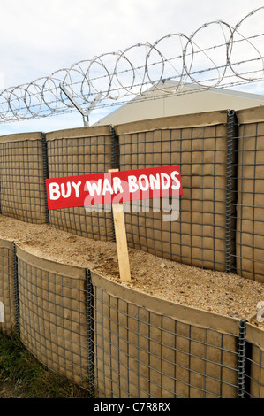 Old-fashioned Buy War Bonds sign in barricade with barb wire on military base. USA. - Stock Photo